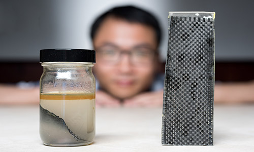 A research team at Georgia Tech has developed a new way of recycling carbon. Pictured above, one of the men involved in the project Kai Yu shows off the team's method - immersing carbon fibre composites in alcohol.